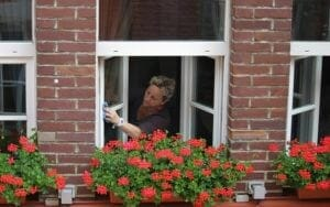Picture of woman cleaning windows in front of red flower box