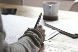 Picture of woman with a pen in her hand writing on some papers on the desk with a cup of coffee in the distance